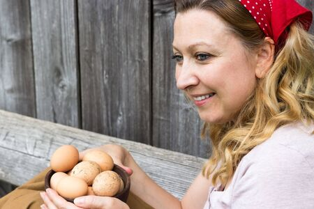 collects: Young farmer smiling and holding a bowl of eggs in her hands
