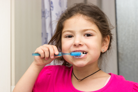 A little girl brushing her teeth in the bathroom Stock Photo