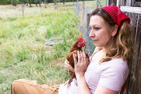 proliferation: A peasant woman holds a chicken in his hands and looks into the distance Stock Photo
