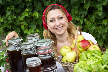 likeable: A market woman with many jars of honey and a basket of apples Stock Photo