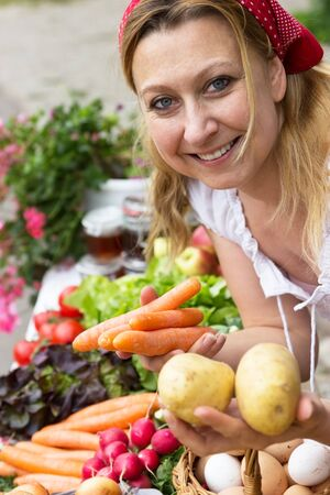 likeable: Peasant woman holding carrots and potatoes in her hands Stock Photo