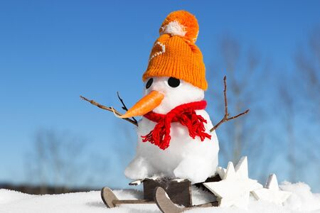 frozen winter: A snowman with knitted hat and scarf sits on a sled Stock Photo