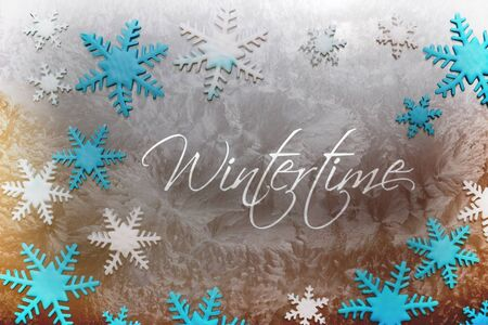 wintertime: Snow crystals of different colors on an icy surface with the inscription Wintertime Stock Photo