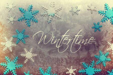 wintertime: Snow crystals of different colors on an icy surface with the inscription Wintertime in vintage look