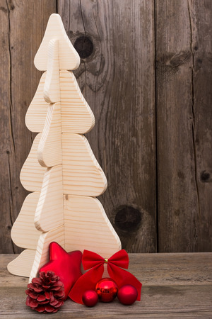 A Christmas tree made of wood against a wooden background