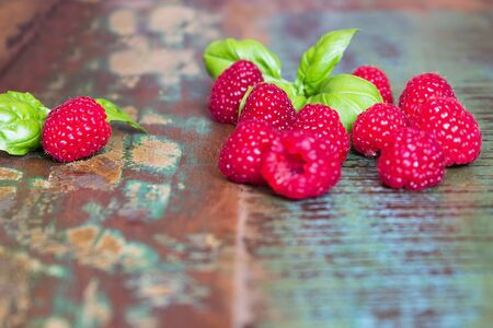 biologically: Several raspberries on a wooden table in a vintage style Stock Photo
