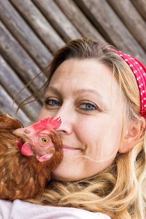 biologically: Young farmer holding a chicken in her arms and looking into the camera