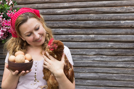 biologically: A young peasant woman holding a bowl of eggs and a hen