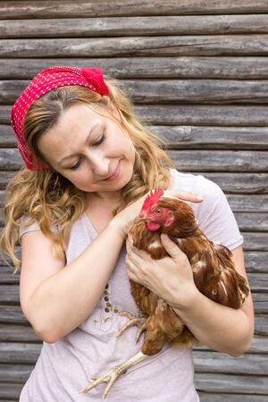 biologically: Young farmer holding a hen in her arms