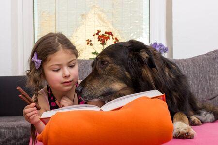 buch: Kind liegt mit einem Hund und einem Buch auf der Couch