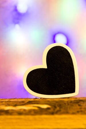 lonliness: A black heart in front of a colorful background on a wooden background