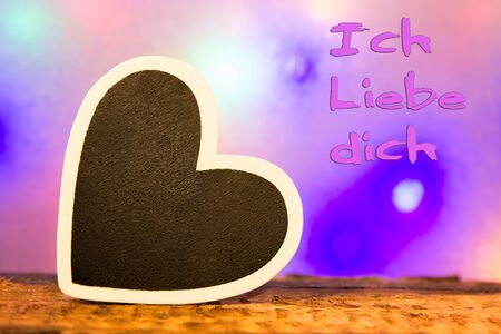lonliness: A black heart with a white border and the inscription Ich liebe dich (I love you in german) Stock Photo