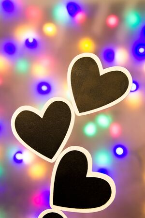 lonliness: Several black hearts against a colorful background