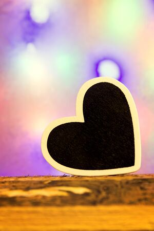 lonliness: A black heart with white border in front of a colorful background Stock Photo