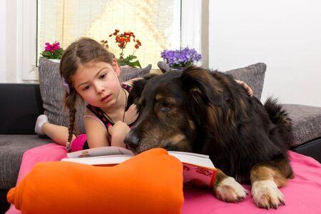 buch: Ein Hund schnüffelt im Buch eines kleinen Mädchens