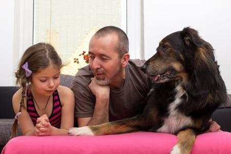 buch: Vater und Tochter liegen mit ihrem Hund auf der Couch Stock Photo
