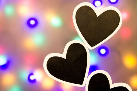 lonliness: Black hearts against a lit background