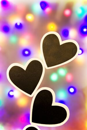 lonliness: Three black hearts with white border against a lit background Stock Photo