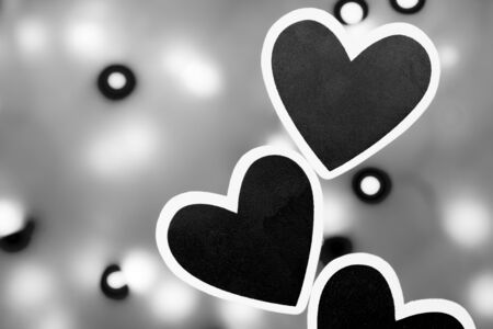lonliness: Several black hearts photographed against a lit background photographed in black and white Stock Photo