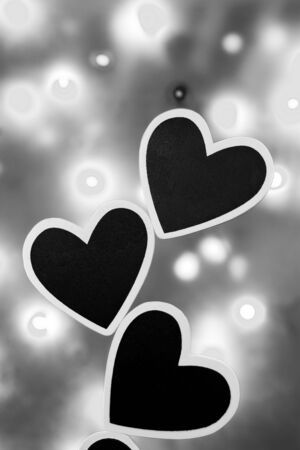 lonliness: Three black hearts against a lit background photographed in black and white