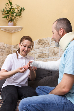 household accident: Follow-up examination of a man with an injury on his arm and neck Stock Photo