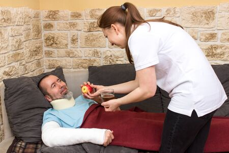 simulate: Injured man on the couch gets an apple and tea Stock Photo