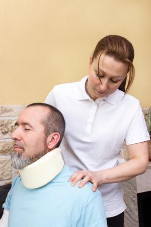 Ein Therapeut massiert den Hals eines Verletzten