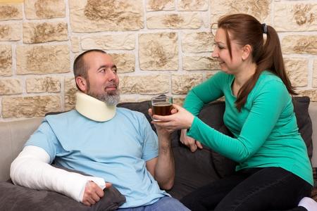 splint: El hombre con el brazo roto y collarín cervical consigue un té