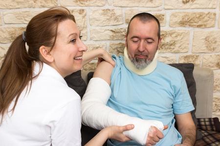 A nurse smiles while examining an injured man