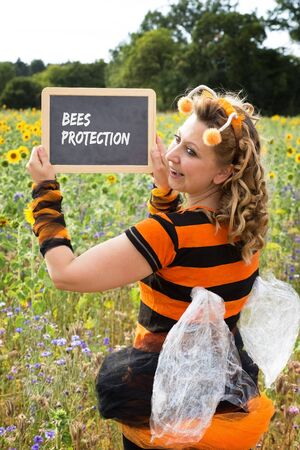 A woman dressed as a bee holds up a shield with bee protection