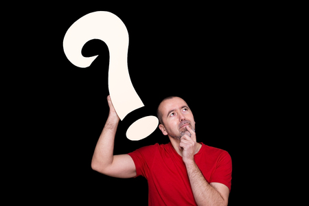 Man thinkingt hard and holding a question mark in his hand Stock Photo