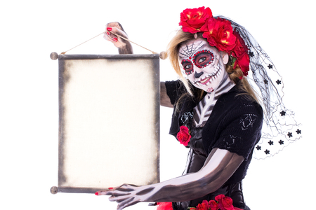 A Sugar Skull holds a scroll in her hands