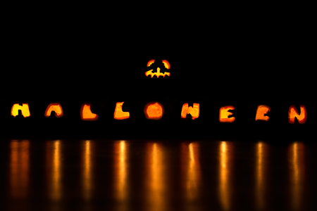 Several hollowed out and illuminated pumpkins form the font Halloween