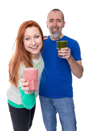 A couple is looking at the camera and everyone is holding a smoothie in their hands