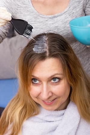 Einer Frau werden die langen Haare gefärbt Standard-Bild - 105855594