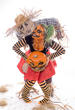 Scary scarecrow and human pumpkin together