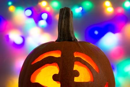 Lighted pumpkin face in front of a colorful background Reklamní fotografie