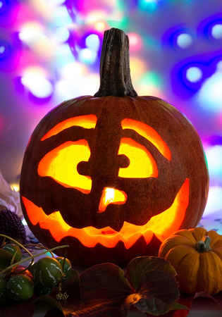Hollowed out pumpkin and several small pumpkins in front of lighted background