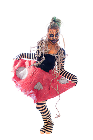 A woman dressed as a pumpkin is dancing against a white background