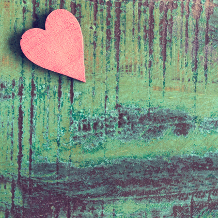 Closeup of a red heart on a green wooden table Stock Photo