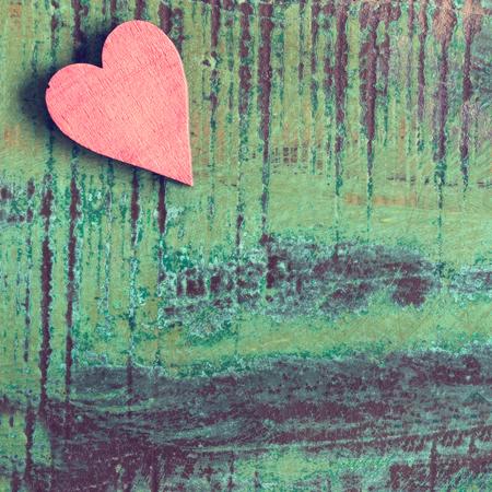 Nahaufnahme eines roten Herzens auf einem grünen Holztisch Standard-Bild