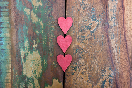 Three red wooden hearts on a colorful table Standard-Bild - 117910044