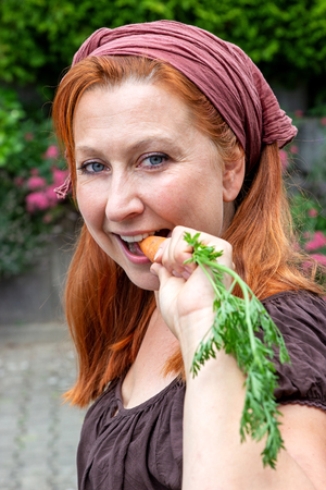 Young attractive farmers wife bites off a carrot Imagens