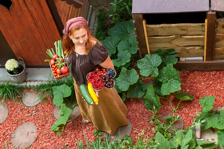 Young peasant woman in the garden carries bowls with fruits and vegetables Imagens