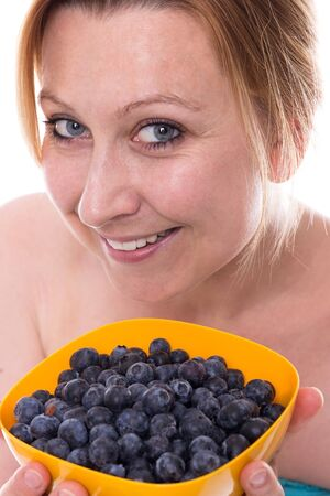 Young attractive woman holds a yellow bowl full of blueberries at the camera Imagens