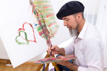 Man with beret paints a picture with hearts