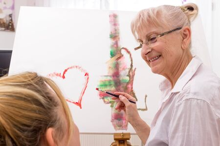 Young woman is watching elderly lady while painting