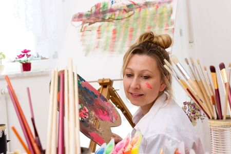Young attractive artist sits at an easel and paints Zdjęcie Seryjne