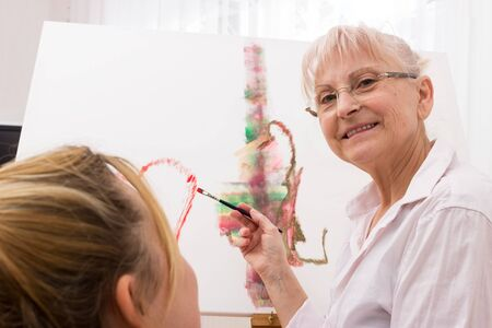 Senior lady with young woman while painting and with eye contact