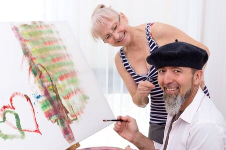 Man in beret sits in front of an easel and smiles at the camera Stok Fotoğraf
